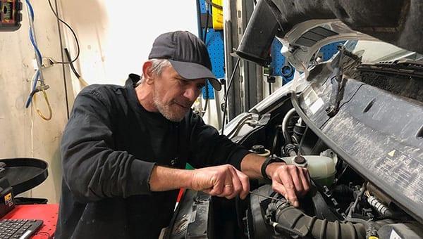 En mann som arbeider med en bil på et verksted